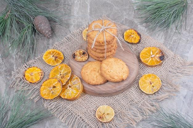 Kekse auf einem holzbrett mit trockenen orangenscheiben herum.