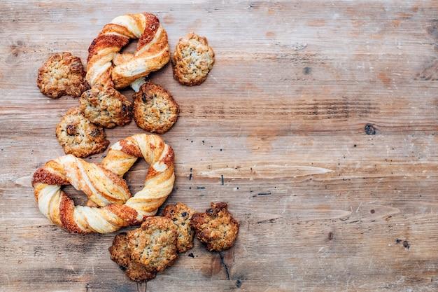 Kekse auf einem rustikalen holztisch. hausgemachte kekse mit nüssen und getrockneten früchten. draufsicht flach lag hintergrund. platz für text. kekse auf holztischhintergrund