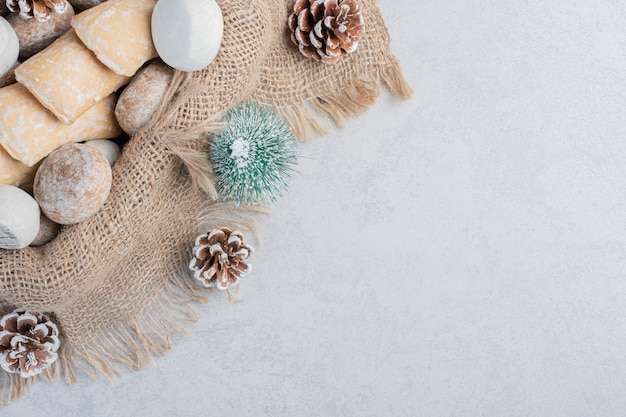 Kekse auf einem stück stoff inmitten von weihnachtsschmuck auf marmoroberfläche gebündelt