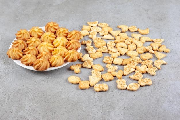 Kekse auf einem teller neben verstreuten keksen auf marmoroberfläche.