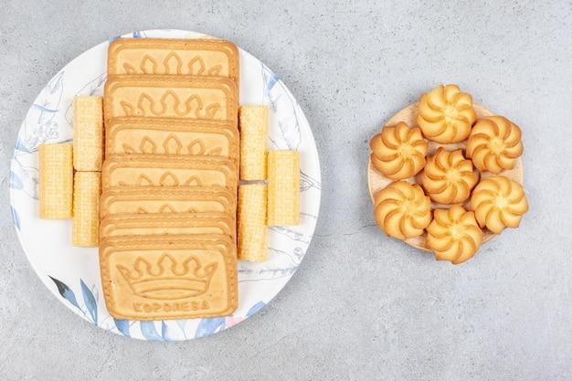 Kekse auf einer kleinen hölzernen untertasse neben keksen, die auf einem teller auf marmorhintergrund aufgereiht sind. hochwertiges foto