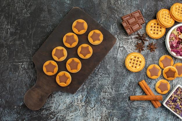Kekse auf holzplatte und trockene blumen auf grau