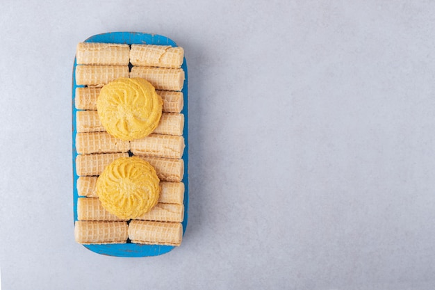Kekse auf waffelröllchen auf dem holztablett, dem marmor.