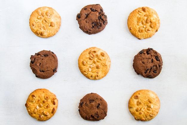 Kekse auf weißem tisch, süßes gebäckdessert mit schokolade und nüssen, draufsicht