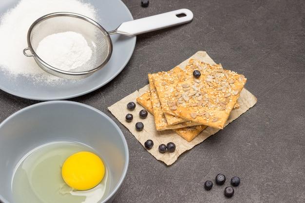 Kekse bestreut mit samen und nudelholz auf dem tisch. mehl und sieb auf grauem teller. zerbrochenes ei und in einer schüssel verquirlen. schwarzer hintergrund. ansicht von oben