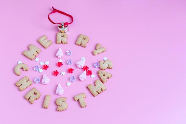 Kekse buchstaben frohe weihnachten auf rosa hintergrund. kreatives weihnachtskonzept.