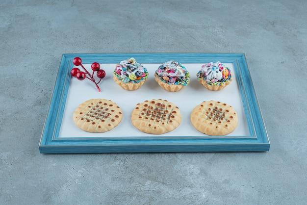 Kekse, cupcakes und eine weihnachtsbeerendekoration auf einem brett auf marmorhintergrund. hochwertiges foto