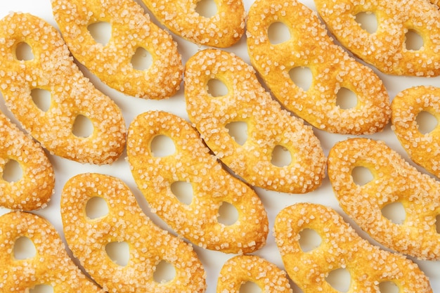 Kekse der gelben farbe, süße brezeln im zucker, große zuckerkristalle, auf weißem hintergrund, isoliert