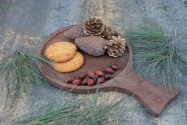 Kekse, getrocknete hagebutten und tannenzapfen auf holzbrett. hochwertiges foto