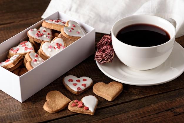 Kekse herzen mit zuckerguss in weißer box und tasse roten tee und rose auf hölzernem hintergrund für valentinstag