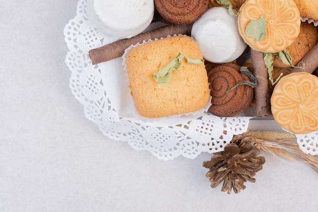 Kekse im seil mit tannenzapfen auf weißer oberfläche