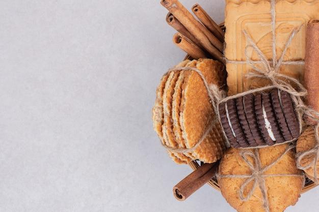 Kekse im seil mit zimt auf weißer oberfläche