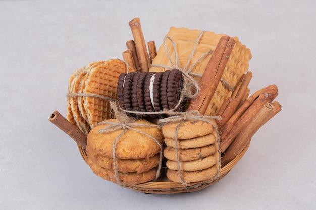 Kekse im seil mit zimtstangen auf weißem tisch.