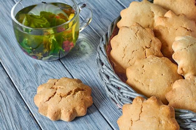 Kekse im weidenkorb aus zeitungsröhrchen und einer transparenten tasse grünem tee