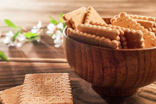 Kekse in einem holzteller auf dem tisch mit einem blühenden zweig