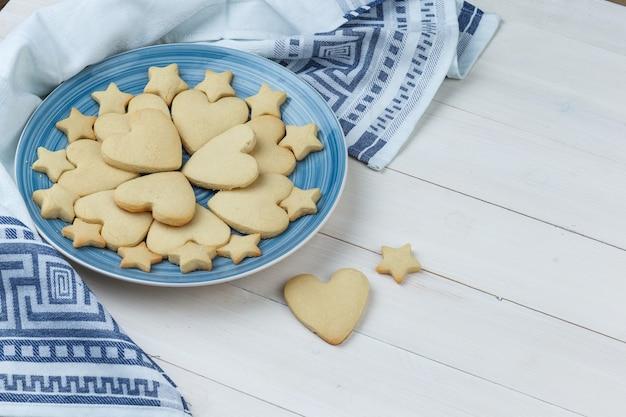 Kekse in einem teller auf holz- und küchentuchhintergrund. high angle view.