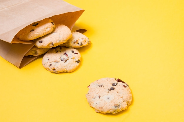 Kekse in einer papiertüte auf einem gelben hintergrund kopieren raumgesunder snack