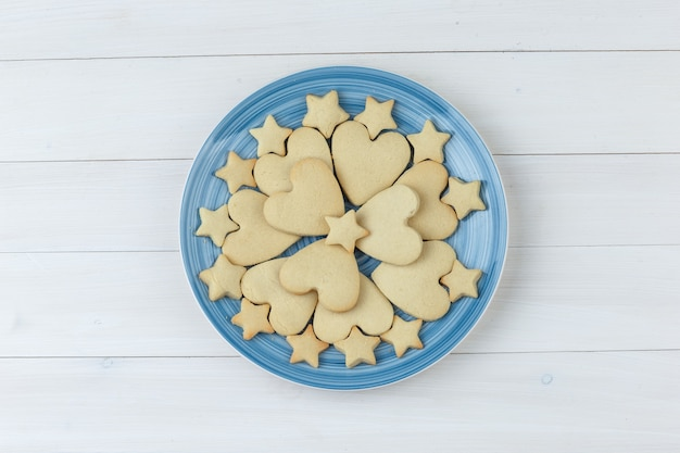 Kekse in einer platte auf einem hölzernen hintergrund. draufsicht.