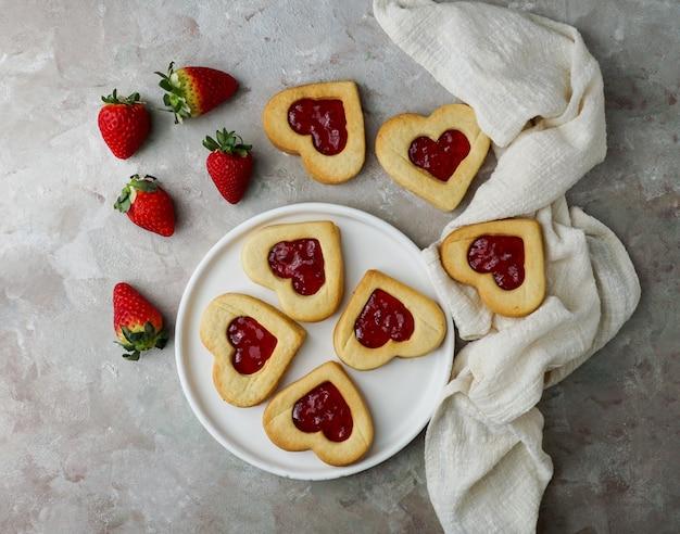 Kekse in form von herzen mit erdbeermarmelade, valentinstag consept