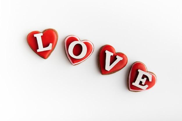 Kekse in form von herzen und inschrift liebe auf weißem hintergrund. valentinstag.