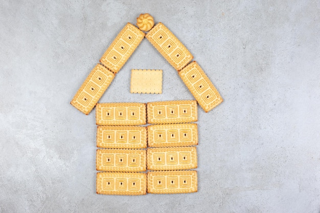 Kekse in hausfigur auf marmorhintergrund angeordnet.