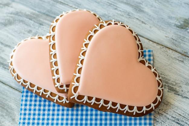 Kekse in herzform. glasierte kekse auf einer serviette. finde liebe und sei glücklich. das stärkste gefühl.