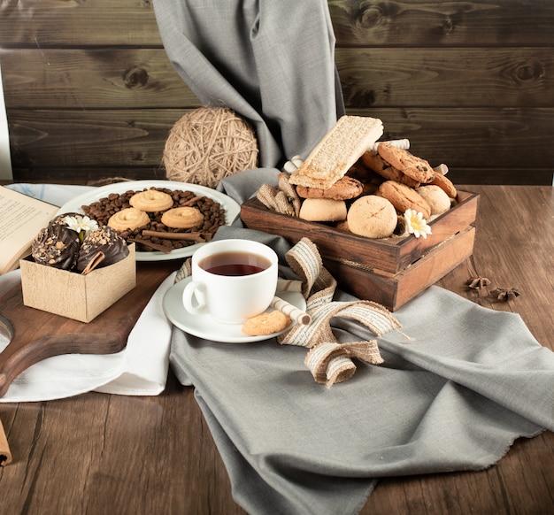 Kekse in rustikalen tabletts und eine weiße tasse tee