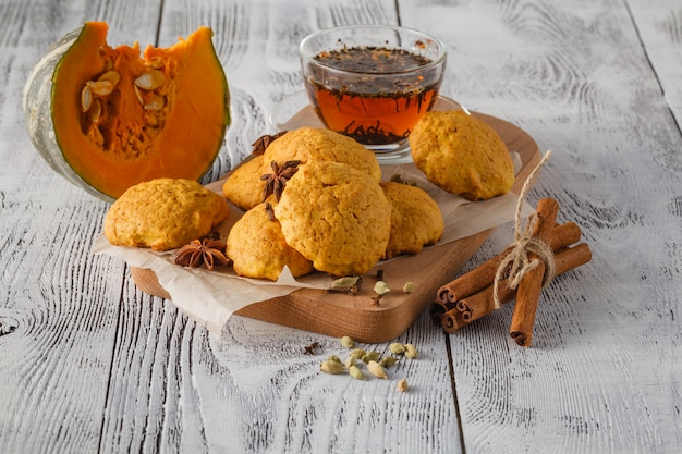 Kekse kürbis und zimt auf dem teller, braune tasse auf holzbrettern hintergrund