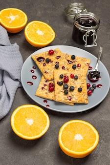 Kekse mit beeren und löffel mit marmelade auf grauem teller. orange hälften und graue serviette auf dem tisch. marmeladenglas. schwarzer hintergrund. ansicht von oben