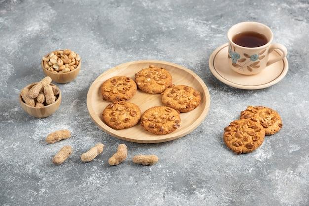 Kekse mit bio-erdnüssen und honig auf holzbrett mit tasse tee.
