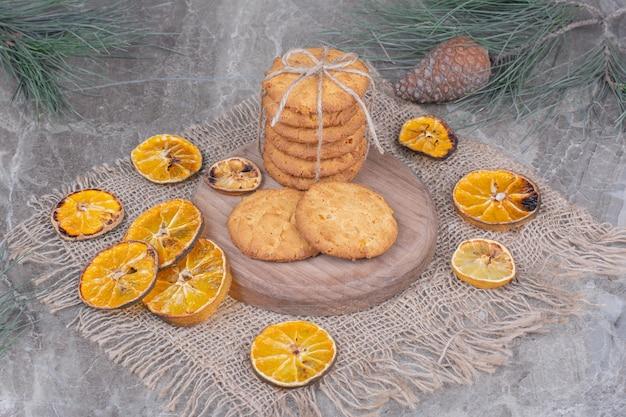 Kekse mit einem faden auf einem holzbrett mit trockenen orangenscheiben gebunden