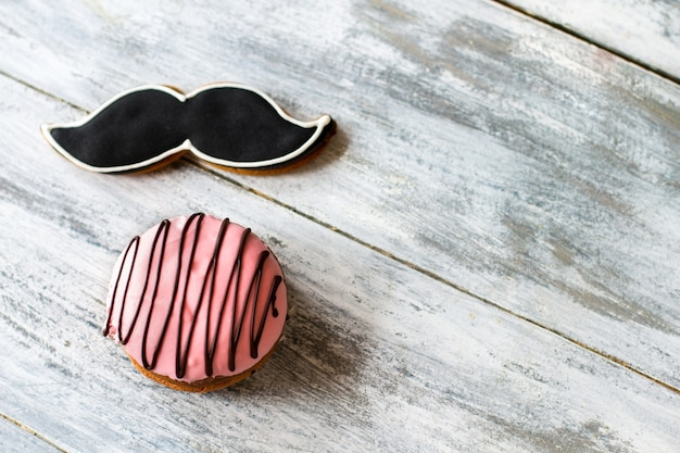 Kekse mit glasur. süßigkeiten auf hölzernem hintergrund. schnurrbartplätzchen und buschkuchen. wahl des herrn.