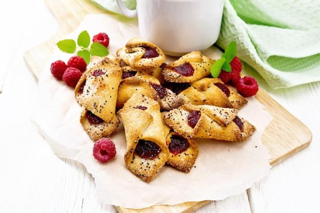 Kekse mit himbeermarmelade, beeren und minze auf pergament auf einem brett, eine tasse mit kaffee und serviette auf weißem holzbretthintergrund
