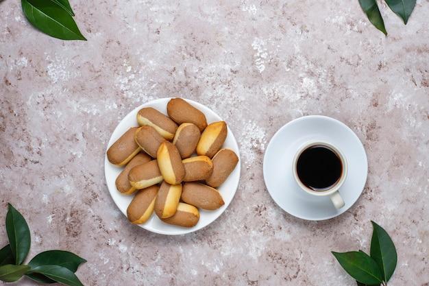 Kekse mit himbeermarmeladenfüllung und gefrorenen himbeeren auf hellem hintergrund, draufsicht