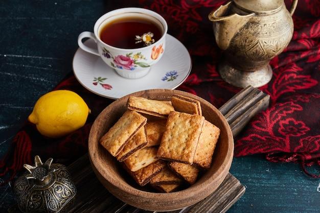 Kekse mit kakao, die eine hölzerne tasse mit einer tasse tee füllen.