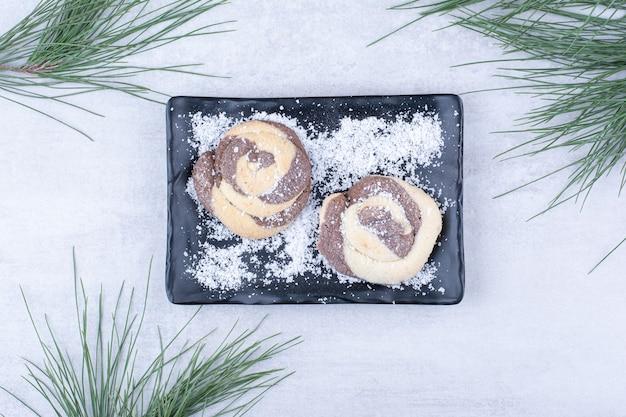 Kekse mit kokosnusspulver auf schwarzem teller