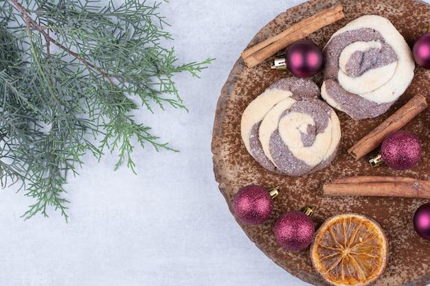 Kekse mit kugeln, zimt und orangenscheiben auf holzstück.