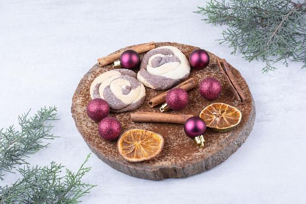 Kekse mit kugeln, zimt und orangenscheiben auf holzstück