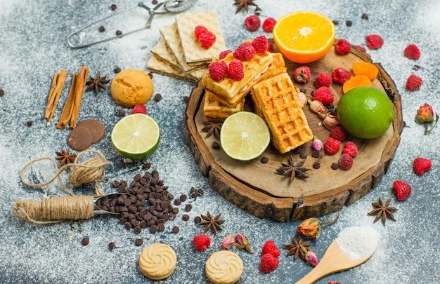 Kekse mit mehl, kräutern, früchten, gewürzen, schoko, sieb flach lagen auf holzbrett und stuckhintergrund