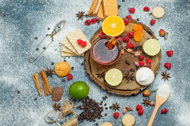 Kekse mit mehl, tee, früchten, gewürzen, schoko, sieb auf holzbrett und stuckhintergrund, draufsicht.