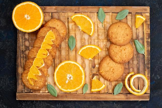 Kekse mit orangengeschmack aus der draufsicht mit frischen orangenscheiben auf der dunklen hintergrundkekszuckerfrucht