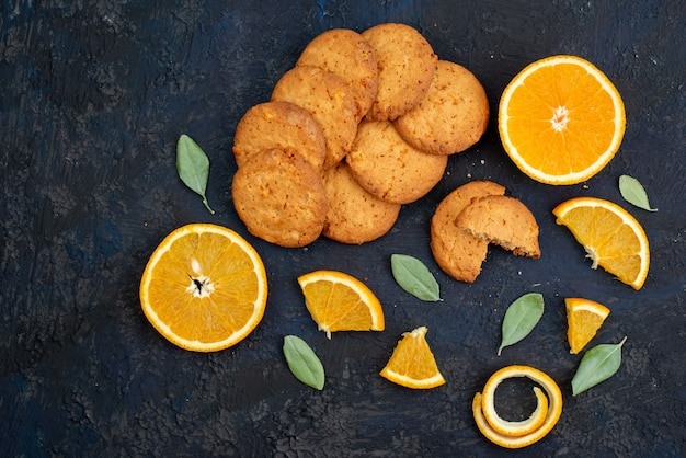 Kekse mit orangengeschmack aus der draufsicht mit frischen orangenscheiben auf der keksfrucht des dunklen hintergrundplätzchens
