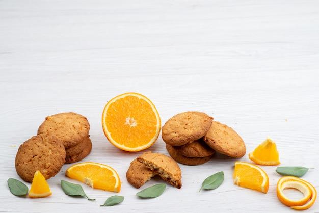 Kekse mit orangengeschmack aus der vorderansicht mit frischen orangenscheiben auf dem leichten schreibtischfruchtkekskeks