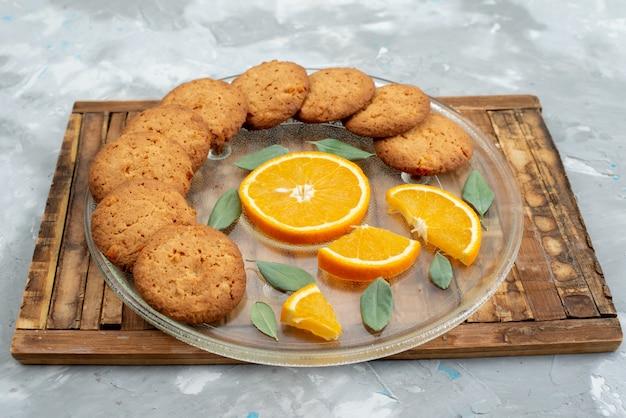 Kekse mit orangengeschmack aus der vorderansicht mit frischen orangenscheiben in der platte auf dem hölzernen schreibtischkekskeks