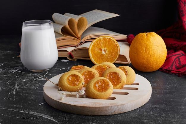 Kekse mit orangenmarmelade serviert mit einem glas milch.