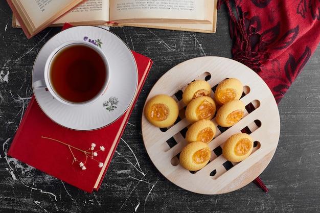 Kekse mit orangenmarmelade serviert mit einer tasse tee, draufsicht.