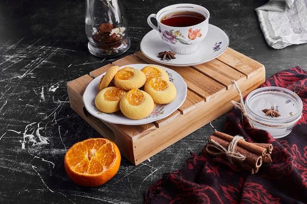 Kekse mit orangenmarmelade, serviert mit einer tasse tee.
