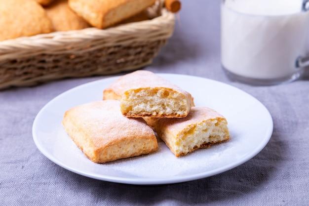 Kekse mit puderzucker auf einem weißen teller. im hintergrund ein korb mit keksen und eine tasse milch. nahansicht.