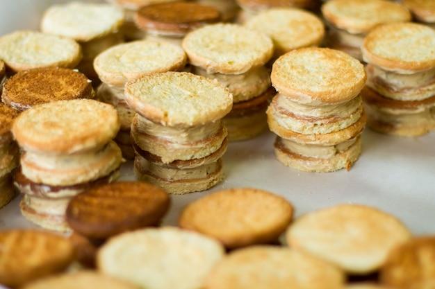 Kekse mit sahne. viele gelbe kekse. snacks für die hausparty. teig und vanillepudding.