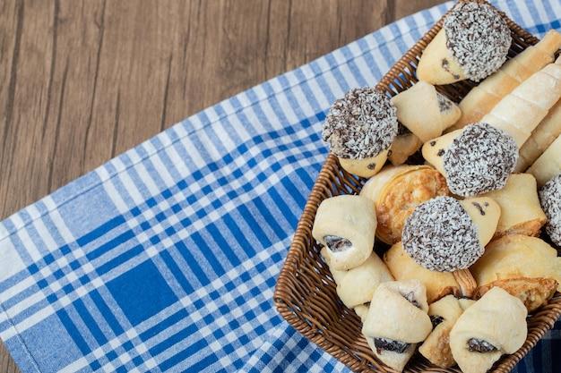 Kekse mit schokolade und gehackter kokosnuss auf holzkorb.